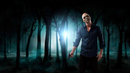 psychopathe: psychopathe avec un pistolet en face des bois fantasmagoriques