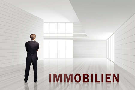 undertaker: businessman in an empty white room with the word Real Estate in German