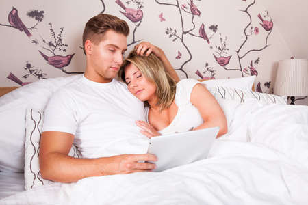 sleeping tablets: young couple in bed, reading and sleeping