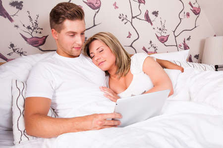 couple in bed, reading and sleeping photo