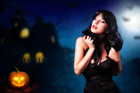 ghoulish: attractive woman in front of a halloween house