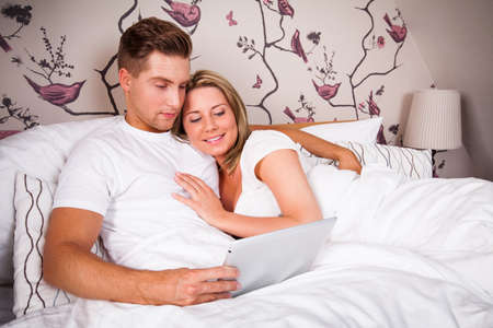 entwined: couple in bed reading on a tablet computer Stock Photo