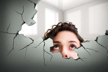 Frau, die durch ein Loch in einer Wand Standard-Bild