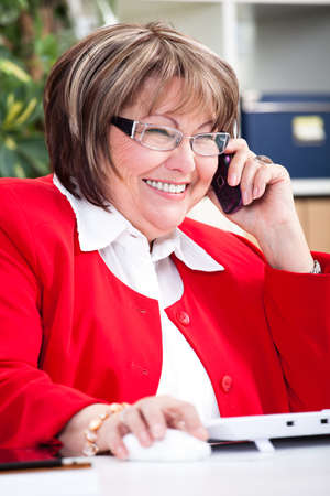 telephoning: senior smiling, telephoning and surfing businesswoman in an office Stock Photo