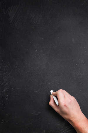 pedagogic: empty blackboard with a hand starting to write