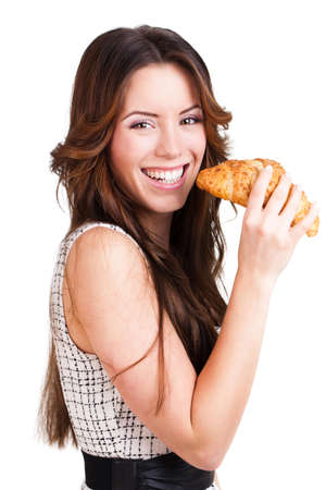 bakery products: attractive brunette woman eating a croissant on isolated background