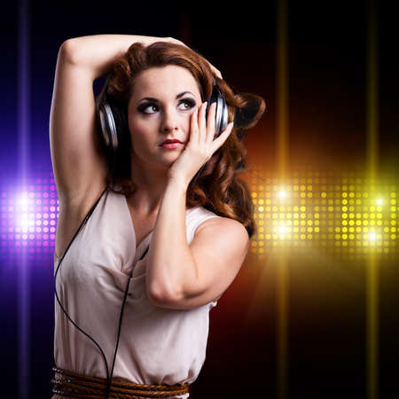 ravishing: young woman with headphones in front of a club background Stock Photo