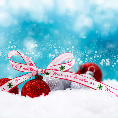 christmas balls in the snow with a merry christmas ribbon