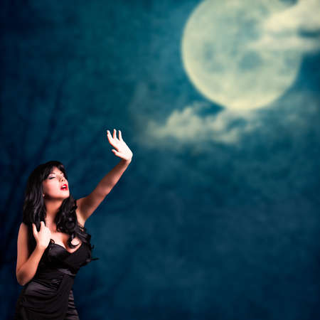attractive black haired woman and a full moon Stock Photo