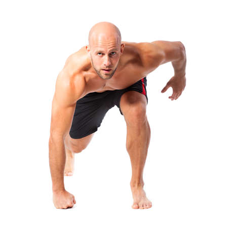 crouches: athletic runner in starting position on isolated background