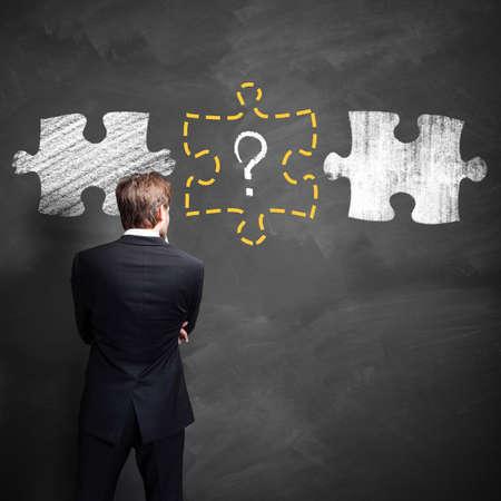 Geschäftsmann denkt über eine fehlende Stück eines Puzzles