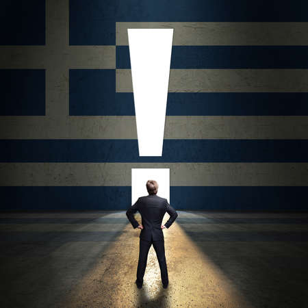 businessman standing in front of a portal shaped as a exclamation mark in a wall painted with the greek flag