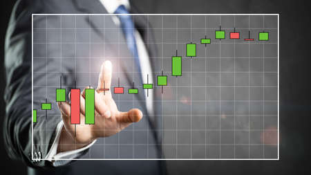 candlestick: businessman touching a stock price chart