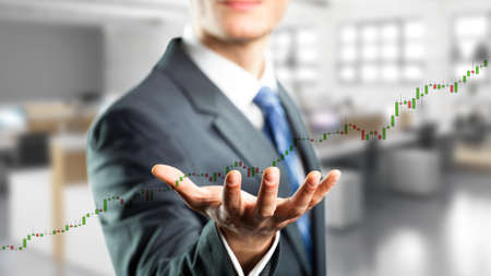businessman holding a virtual stock price chart