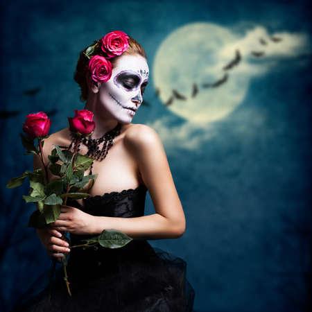 mujer con rosas: Mujer atractiva con el cráneo de azúcar maquillaje