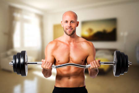 muscle toning: muscular man with a barbell during a workout