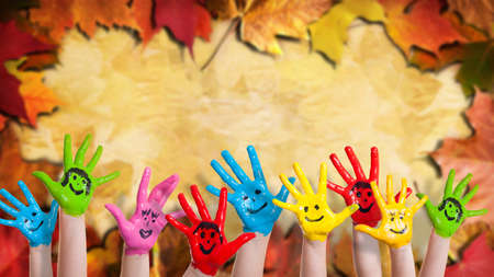 painted: colorful painted hands in front of many colored leafs Stock Photo