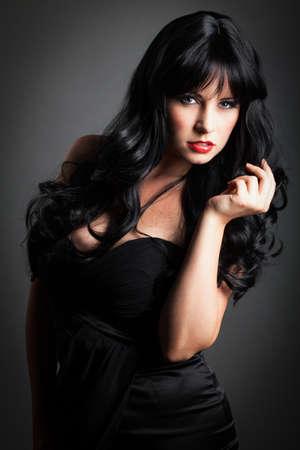 cabello negro: Mujer atractiva con el pelo largo y negro en un vestido negro