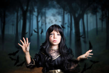creepy: young girl dresses as a witch in a creepy forest
