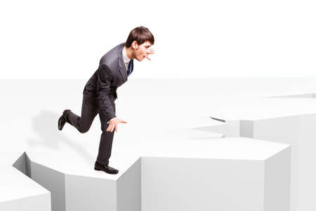 overbalance: businessman balancing to not fall into an abyss