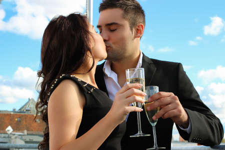 drinks after work: flirting couple with sparkling wine on a roof