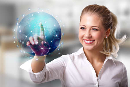 emigration: businesswoman touching a holographic globe in front of an office scene