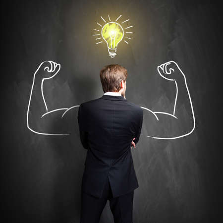 successful businessman standing in front of a blackboard with a drawn lightbulb, symbolizing having an idea Stock Photo