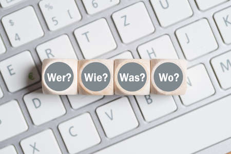 an answer: cubes with the words who, how, what, when in German on a keyboard