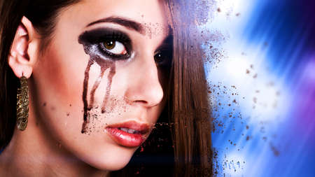 cheek: young brunette woman with black tears on her cheek