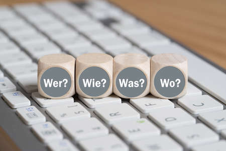 cubes with the words who, how, what, when in German on a keyboard