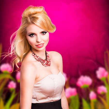 evening wear: attractive woman in evening wear in front of a painted floral background Stock Photo