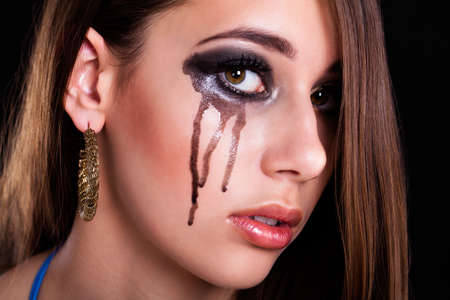 bereaved: young brunette woman with black tears on her cheek
