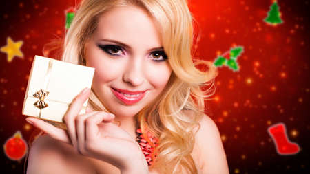 evening wear: attractive woman in evening wear with a gift in front of a christmas background Stock Photo