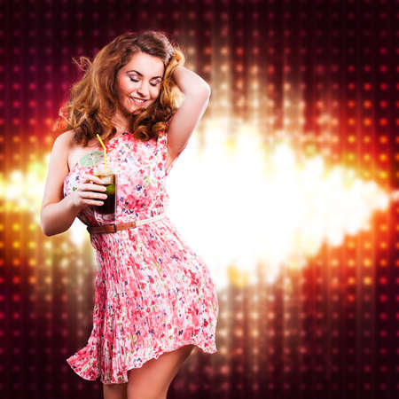 ravishing: young woman with a drink in front of a club background