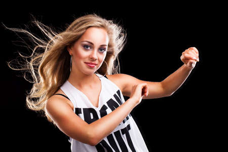 moves: young blonde dancing girl on black background Stock Photo