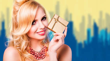 evening wear: attractive woman with a gift in evening wear in front of a painted cityscape