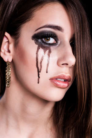 downhearted: young brunette woman with black tears on her cheek