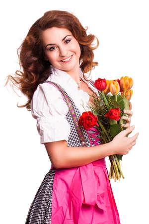 mujeres felices: hermosa mujer en un dirndl bávaro tradicional con un ramo de tulipanes aislado en blanco