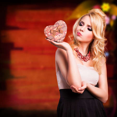 evening wear: attractive woman in evening wear with a heart shaped gift box