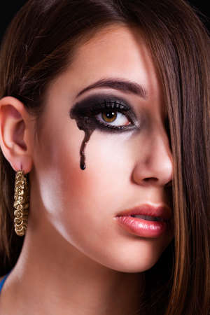 bereaved: young brunette woman with a black tear on her cheek
