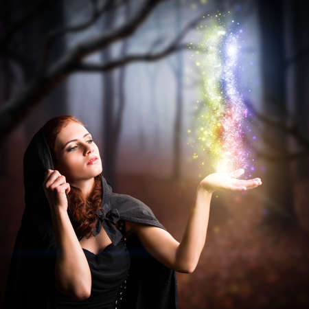 attractive woman dressed as a witch in a forest with magical lights