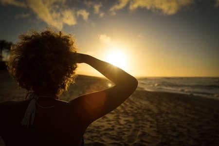 mujer mirando el horizonte: mujer joven mirando el atardecer en la playa de la puesta del sol, Hawai