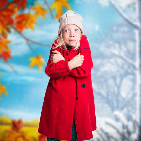 adorable young girl in winter clothes freezing in front of background with changing seasons