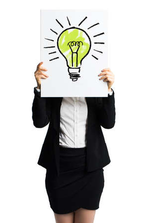 envisage: businesswoman holding a  white card with a drawn lightbulb in front of her
