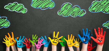 painted kids hands in front of a blackboard
