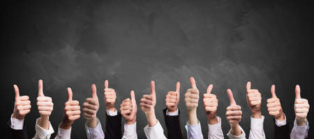 many thumbs up in front of a blackboard