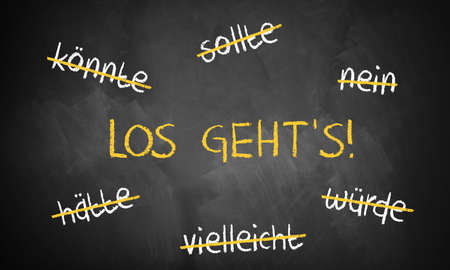 dedicate: chalkboard with stroked words like could and should and Lets go in the middle in German