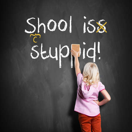 elementary school: young girl correcting mistakes in the sentence School is stupid Stock Photo