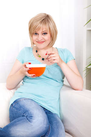 energising: young blond woman on a couch eating breakfast Stock Photo