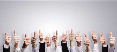 many thumbs up in front of a grey background Stock Photo